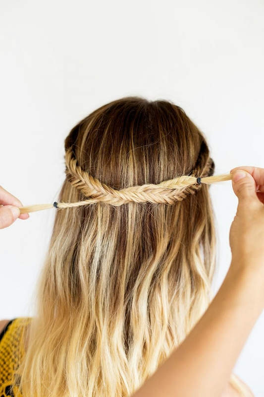 Βήμα 5: Όταν τελειώσετε με το πλέξιμο της δεύτερης πλεξούδας, παίρνετε τις δυο fishtail braids και τις δένετε σε ένα κόμπο.