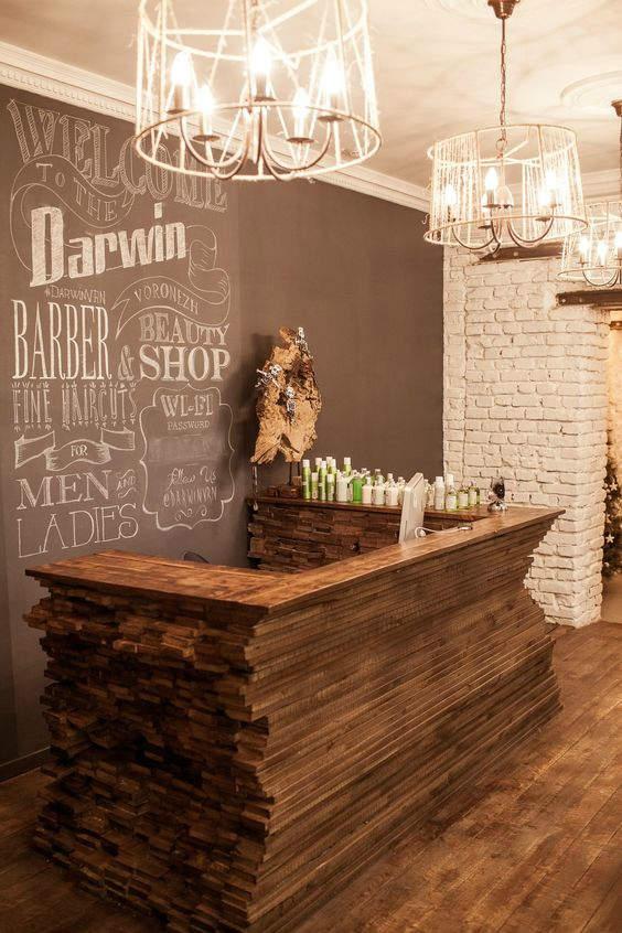 Ιδιαίτερο waiting room ενός barber shop, όπου το γραφείο αποτελείται από ξύλινες πλάκες, ενώ ο τοίχος φέρει DIY διακόσμηση, αφού έχει γραφτεί με κιμωλία.